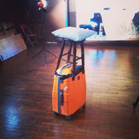 A camera dolly made from a stool taped to rolling luggage.