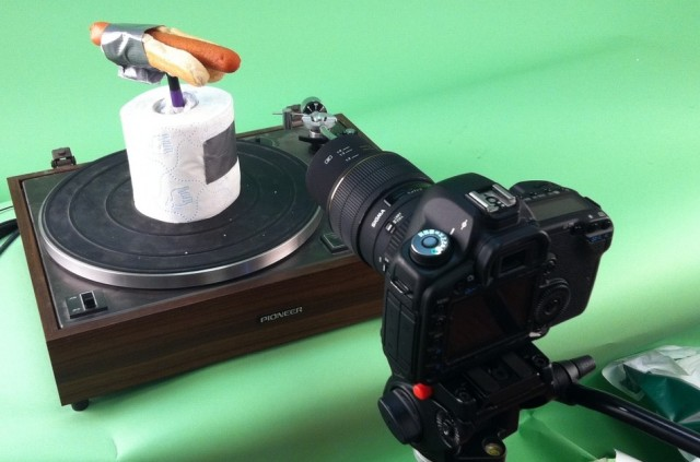 A hotdog taped to toilet paper on a record player.